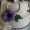 A two tier wedding cake decorated with fondants flowers and edible sparkles.