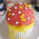 One giant cupcake adorned with butterflies and beads